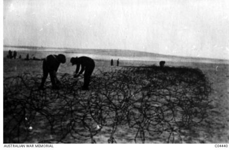 5th FCE putting down wire entanglements. Photographer unknown, photograph source AWM C04440