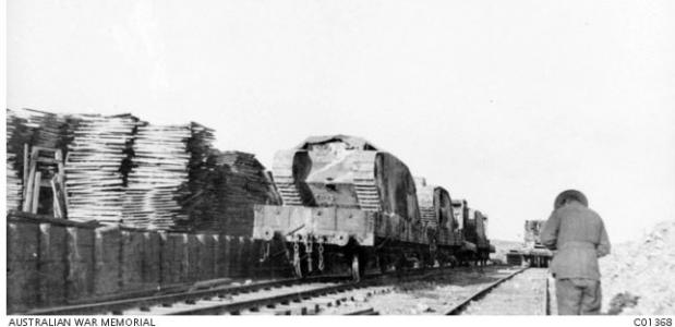 Damaged tanks from Pozieres loaded onto flat cars Australian Light Railway Corps. Photographer unknown, photograph source AWM C01368